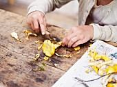 A girl cutting chanterelle mushrooms on a wooden table