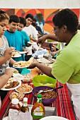 Woman serving people food in buffet