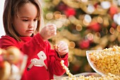 Caucasian girl stringing popcorn at Christmastime
