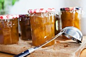 A few jars of greengage jam on a chopping board