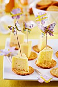 Butterfly shapes punched out of map decorating toothpicks stuck in cheese