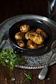 Roasted new potatoes in a bowl with sea salt and greek basil.