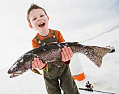 A little boy with a freshly caught fish caught while ice fishing