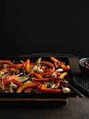 A pumpkin-fennel medley with garlic and bacon on a baking tray