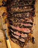 Overhead of London Broil steak sliced on a cutting board with carmelized onions and a vintage carving fork