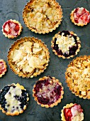 Various tartlets: berry tartlets, crumble tartlets and tartlets topped with slivered almonds