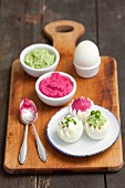 Boiled eggs with three dips: beetroot dip, horseradish dip and pea dip