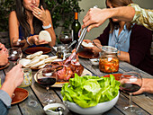 Friends enjoying a meal of roast, bread rolls, salad, kimchi and red wine at a garden table