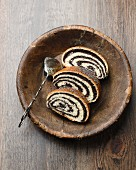 Three slices of poppyseed strudel in a wooden dish