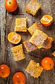 Mandarin cake slices and fresh mandarins (seen from above)