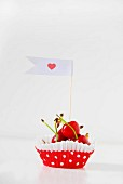Red cherries in a paper paste decorated with a flag and a heart