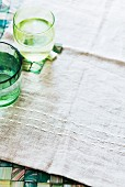 Green water glasses on a beige-coloured linen cloth