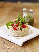 White bread topped with hummus, capers and tomatoes