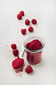 Raspberry fruit powder in a glass and on a spoon
