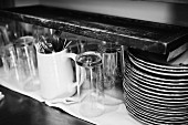 Glasses, cutlery and a stack of plates