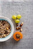 A bowl of muesli next to grapes, nuts and an apricot