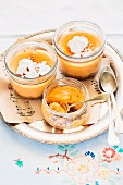Cheese and pumpkin cakes with gingerbread bases in glasses garnished with ricotta