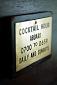 A sign detailing the opening hours of a cocktail bar