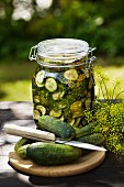 A jar of gherkins with dill on a garden table