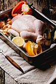 Raw chicken with vegetables in a roasting tin on old wooden table