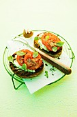 Crostini topped with pesto, cream cheese and tomatoes