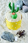 A lemon cupcake decorated with a cactus