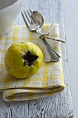 A quince and cutlery on a napkin