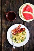 Scrambled eggs with onions, peppers and bacon next to a plate of watermelon and a cup of tea on a wooden table