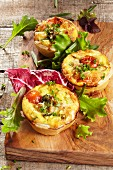Three mini vegetable quiches with a salad garnish on a wooden board