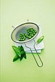 Fresh peas in a sieve next to mange tout
