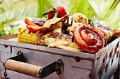 Chicken, beef, sausages, corn on the cob and vegetables on a barbecue tray