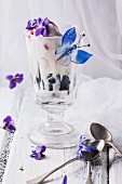 An ice cream sundae with vanilla ice cream, fruit jelly and blueberries, and decorated with sugared violets