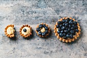 Various different sized blueberry tartlets with lemon cream, one with a bite taken out