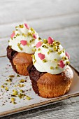Marble cupcakes topped with white cream, pistachios and pink sugar Christmas trees
