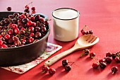 Cherries in a deep cast iron pan with a cup of sugar and a wooden spoon