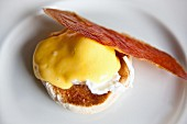 A bird's-eye view of eggs Benedict with a slice of crispy Parma ham
