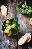 Grape and spinach salad served in a coconut shell on a wooden surface