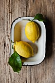 Two lemons with leaves in a bowl