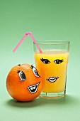 An orange and a glass of orange juice with faces