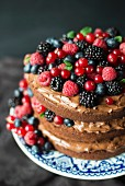 A layered chocolate cream cake decorated with berries and mint leaves