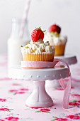 Strawberry yogurt cupcakes decorated with pink bows on cake stands and a bottle of milk with a straw in the background