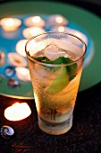 A mojito in front of a pate of tealights