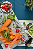 An arrangement of vegetables featuring carrots, radishes and chilli peppers on a chopping board