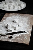 Homemade marshmallows dusted with icing sugar on a chopping board and in a bowl