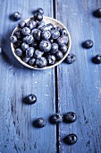 A bowl of blueberries on a blue wooden surface