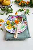 A place setting with tufted pansies and a spoon