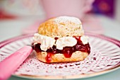 A scone with cream and strawberry jam on a doily with a teacup in the background