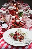 A Christmas table laid with a red checked tablecloth, candles, napkins and jars of jam