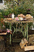 Autumnal bread with rolls, sausages and cake in a garden