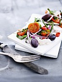Cod salad with onions, olives and tomatoes